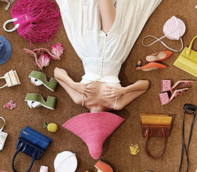 Woman in white dress lying on the floor with a big pink hat on her head covering her face and accessories on the floor around her