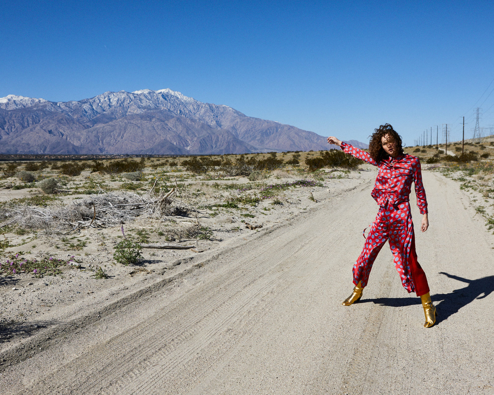 Josh Shinner picture of a woman in pink on an empty road pointing to snowy moutains