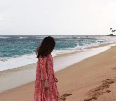 Katie Sharples wearing a pink dress on the beach