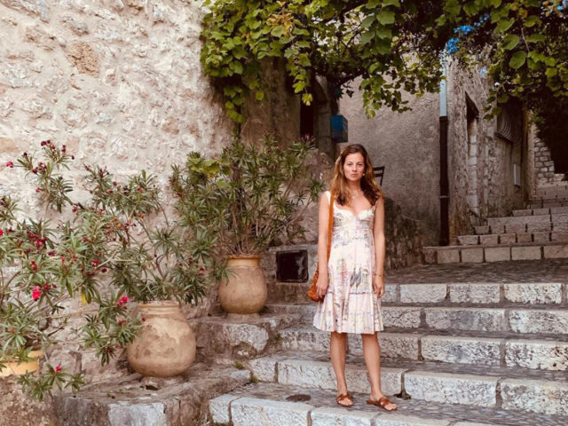 Serena Hood in a dress on outdoor steps with plants