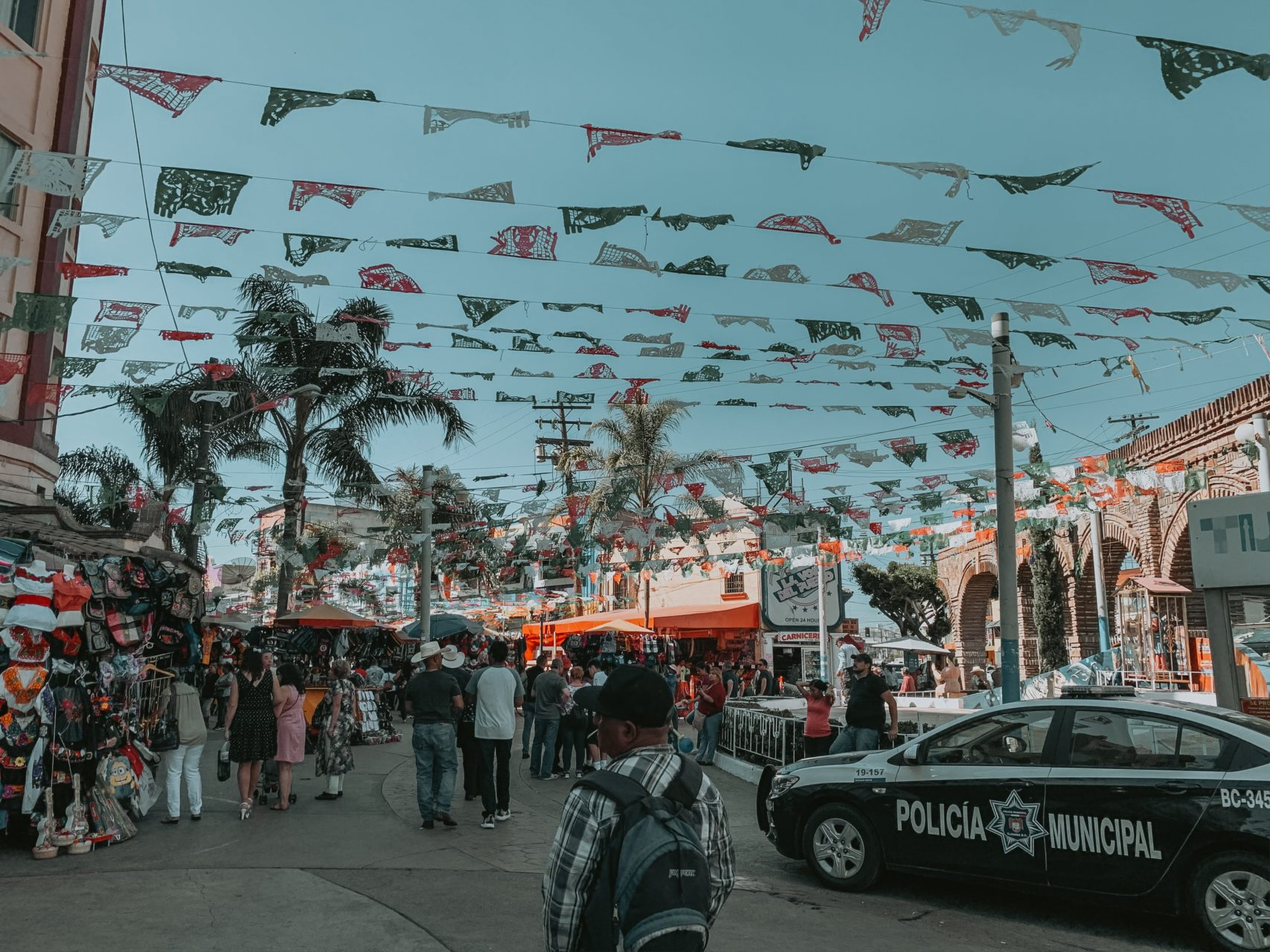 A busy street in Todos Santos, Mexico, with flags and market stalls.